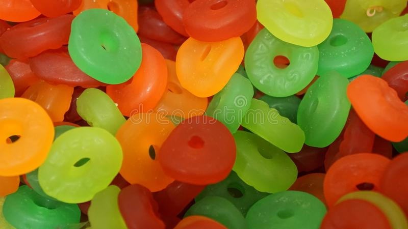 Multi color gummy life savers. Small gummy life savers in different colors stacked together, candies texture background, gelatin donuts in green, yellow, red stock images
