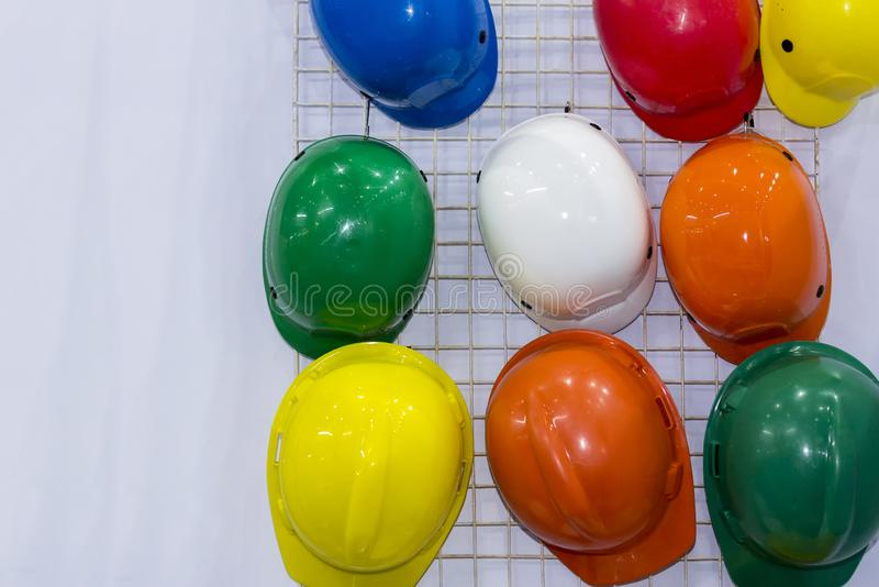 Multi-color helmet hanging on a white wall stock image