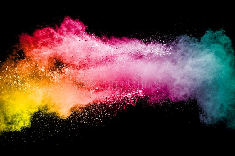 Multi color particles explosion on black background. Colorful dust splatter on dark background royalty free stock photo