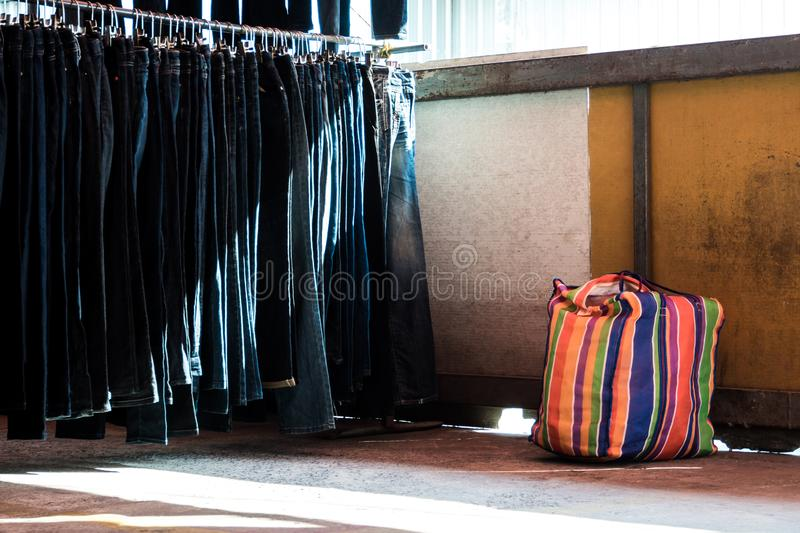 Multi color on Plastic sack and the row of denim pants hanging on trempels. Jeans in clothing store stock image