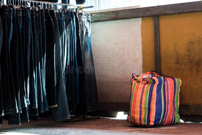 Multi color on Plastic sack and the row of denim pants hanging on trempels of Flea market. Multi color on Plastic sack and the row of denim pants hanging on royalty free stock image