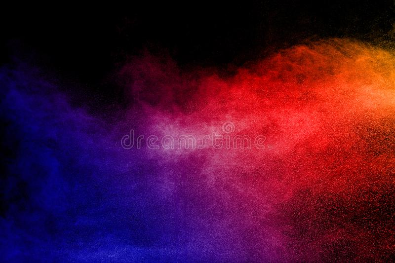 Multi color powder explosion on black background. Color dust particle splattered on dark background royalty free stock photo