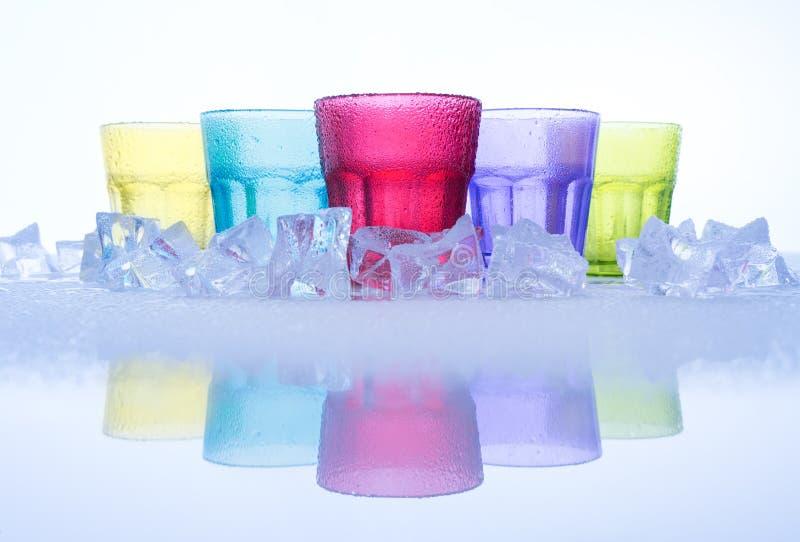 Multi coloreada de los vidrios de agua fresca con el cubo hiela y reflexión en una tabla de cristal, en el fondo blanco fotos de archivo libres de regalías