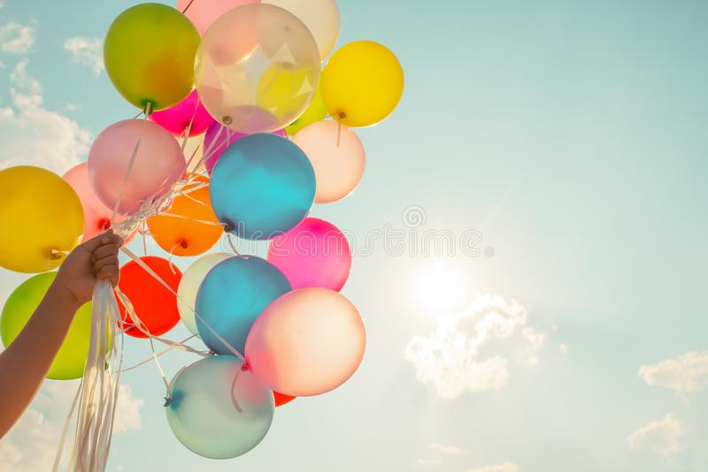 Multi colored balloons done with a retro vintage instagram filter effect. Hand holding multi colored balloons done with a retro vintage instagram filter effect royalty free stock image