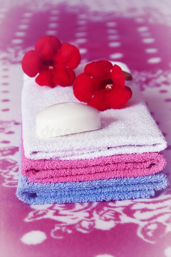Multi-colored bath towels and white toilet soap royalty free stock photos