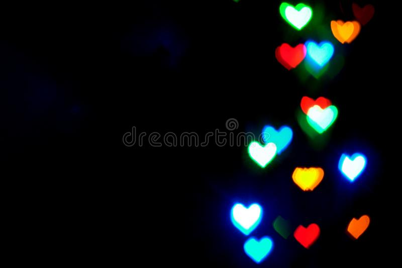Multi colored blurred lights in the shape of hearts in the dark stock images