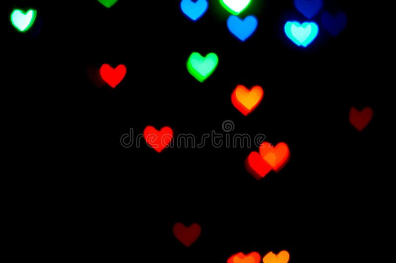 Multi colored blurred lights in the shape of hearts in the dark stock photos