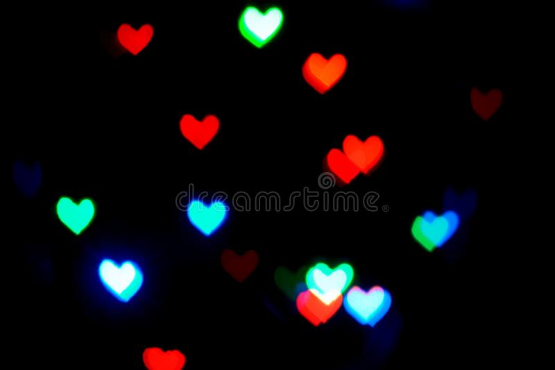 Multi colored blurred lights in the shape of hearts in the dark royalty free stock image