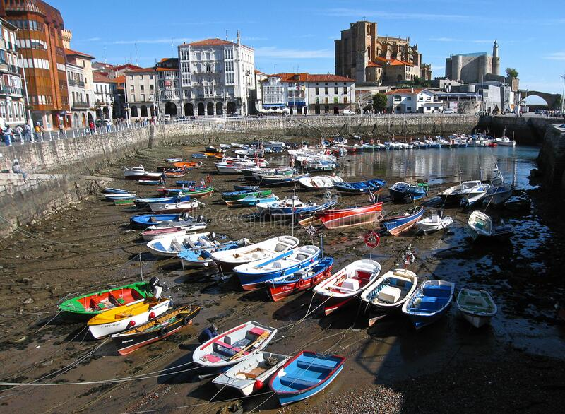 Multi-colored boats in the port of Castro Urdiales at low tide, Spain. Castro Urdiales, Spain - September 28, 2007, Multi-colored boats in the port of Castro stock image