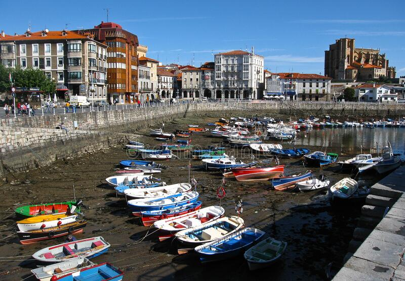 Multi-colored boats in the port of Castro Urdiales at low tide, Spain. Castro Urdiales, Spain - September 28, 2007, Multi-colored boats in the port of Castro royalty free stock photo