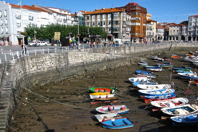 Multi-colored boats in the port of Castro Urdiales at low tide, Spain. Castro Urdiales, Spain - September 28, 2007, Multi-colored boats in the port of Castro royalty free stock images