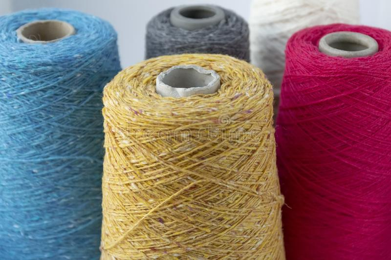 Multi-colored bobbins of wool yarn for hand and machine knitting.  stock images