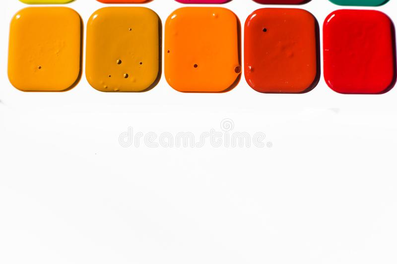 Multi-colored bright Watercolor paints of warm shades close up. A frame from paints on a white background royalty free stock photography