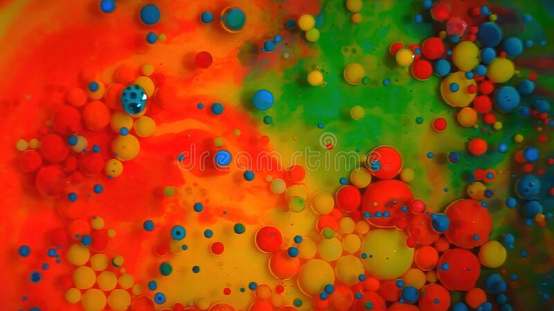 Multi-colored bubbles in the water. Abstract rainbow drops, can be used as background. Vividly beautiful this image is an abstract macro depiction. Still life royalty free stock photography