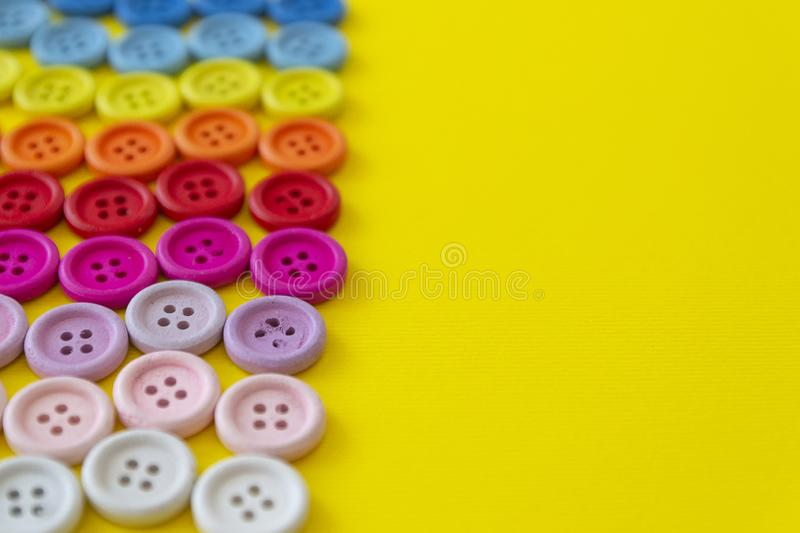 Multi-colored buttons on a yellow background. Button rainbow for clothes. Copy space royalty free stock images