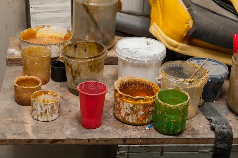 Multi-colored cans and containers with old dried paint and glue of yellow color on the table in the workshop for work with royalty free stock photo