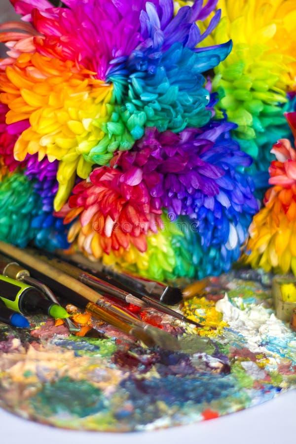 Multi-colored chrysanten op het palet met verven en borstels van de kunstenaar stock afbeeldingen