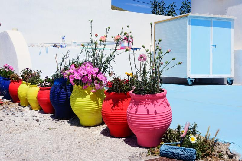 Multi-colored clay pots with flowers under the bright sun. Renovation in a traditional greek house with white and blue paint. Santorini island, Greece. Greek stock photo