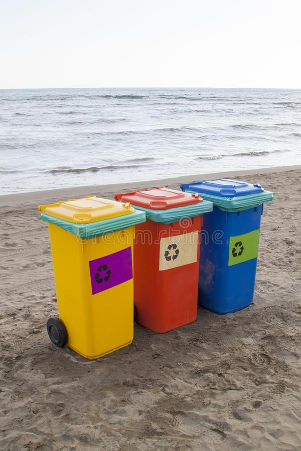Multi-colored containers for sorting garbage are on the beach ag. Ainst the sea, plastic, recycling, blue, yellow, paper, glass, sand, green, waste, outdoor stock image