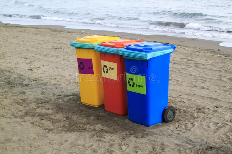 Multi-colored containers for sorting garbage are on the beach ag. Ainst the sea, plastic, recycling, blue, yellow, paper, glass, sand, green, waste, outdoor royalty free stock photography