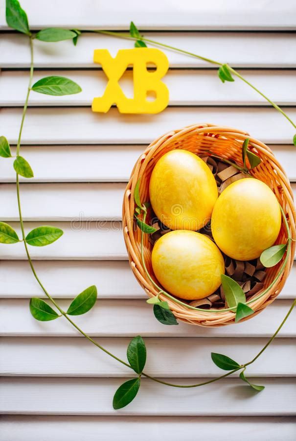 Multi-colored Easter eggs in a wicker basket on a white background stock photo