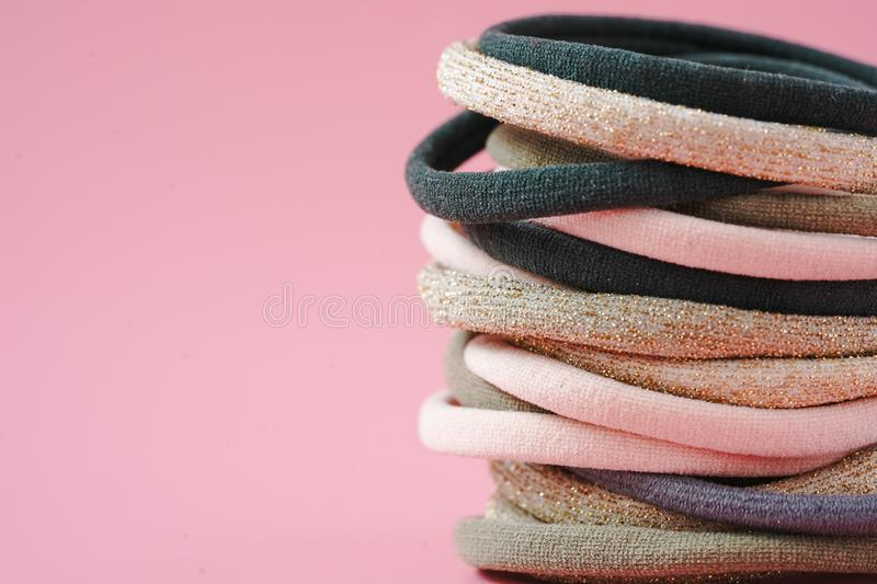 Multi-colored elastin for binding hair on a pink background stock photography
