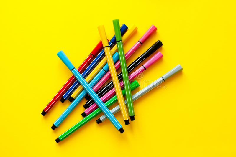 Multi-colored felt-tip pens on yellow background. Top view,business, office supplies. School office supplies. Minimal style. Colo. Rful marker pen set. Vivid royalty free stock photos