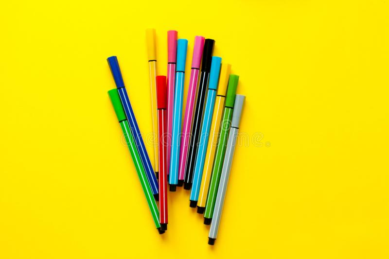Multi-colored felt-tip pens on yellow background. Top view,business, office supplies. School office supplies. Minimal style. Colo. Rful marker pen set. Vivid royalty free stock photography