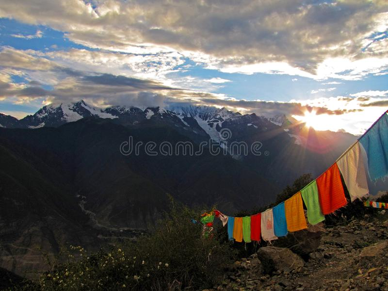 Multi-colored flags with Buddhist sacred texts in sanscrit hung over the mountain slope and illuminated by the rays of sun dur royalty free stock images