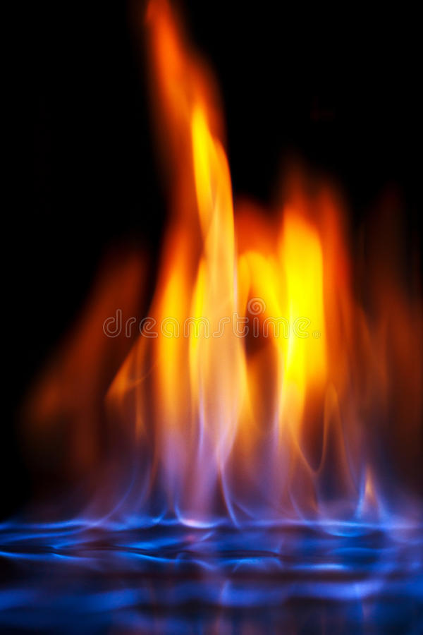 Multi-colored flame of burning alcohol. Blue and yellow colored flames isolated on black background stock image