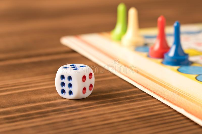 Multi-colored game chips with dice on the playing board. Board game concept royalty free stock photo