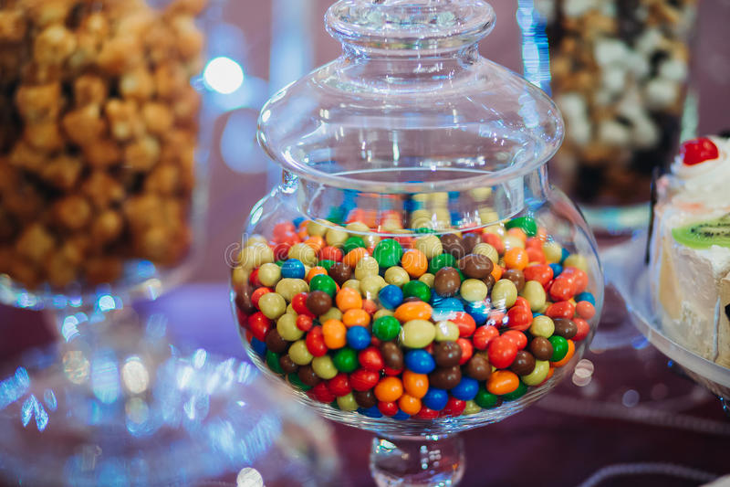 Multi-colored geleibonen, dragee in een fles glas stock afbeeldingen