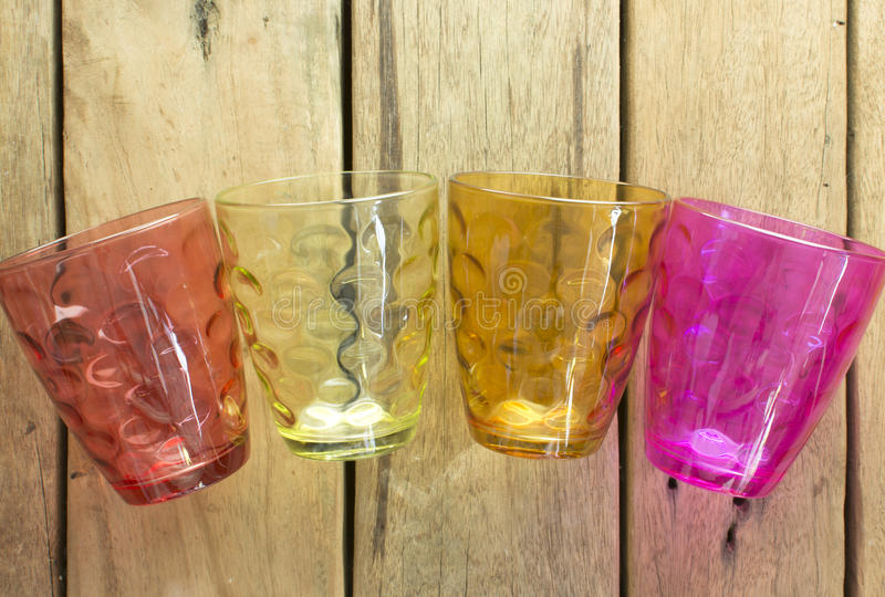 Multi-colored glasses of water, which is placed on a wooden table. stock images