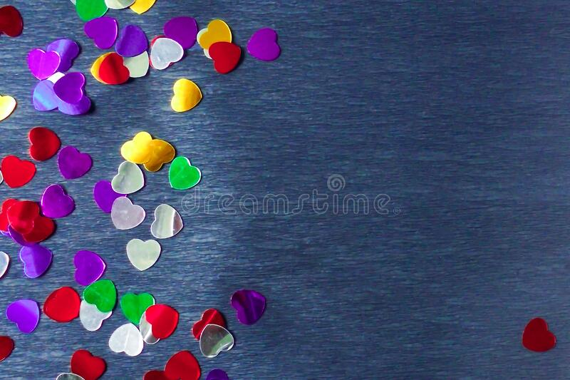 Multicolored foil hearts scattered on a gray background. Multi-colored hearts of blue silver violet purple yellow randomly scattered on a gray background paper royalty free stock photography