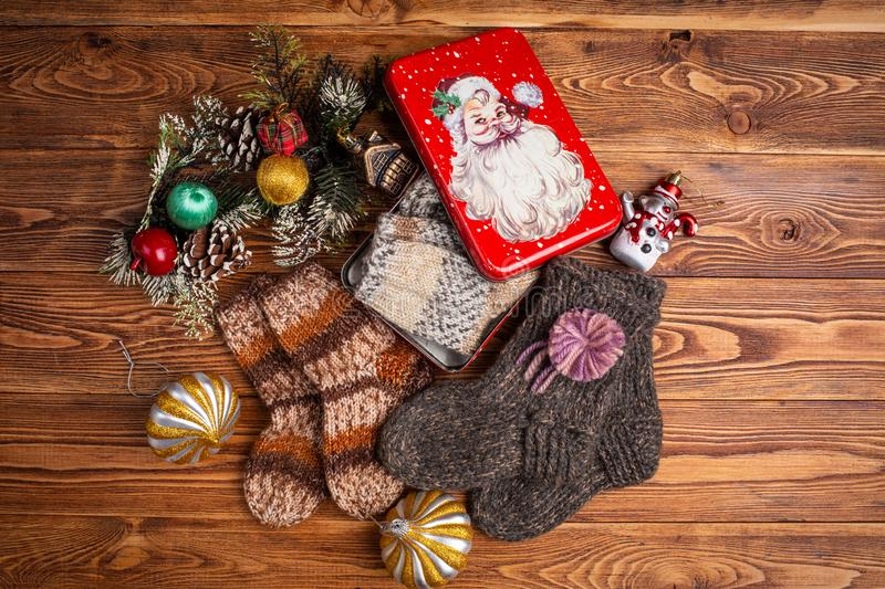 Multi-colored knitted baby socks, Christmas decorations and a metal box with the image of Santa Claus on a wooden background royalty free stock image