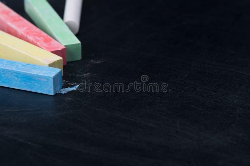 Multi-colored krijt ligt op een zwarte raad, een plaats voor een inschrijving royalty-vrije stock foto