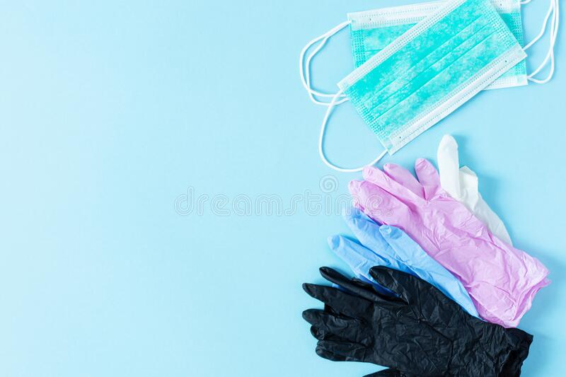 Multi colored surgical gloves and surgical masks on blue background top view. Virus protection concept. Multi colored latex surgical gloves and surgical masks on stock images