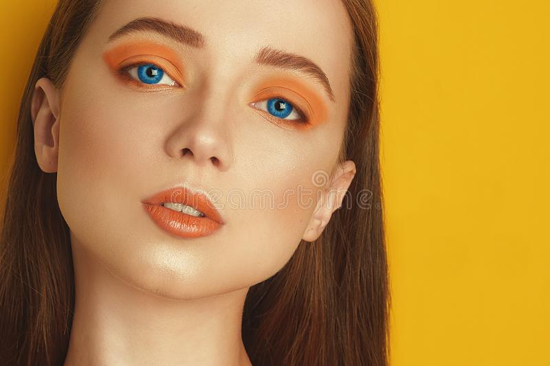 Multi-colored lenses for eyes. Blue lenses, green lenses. Beauty Model Girl with orange professional makeup. Orange eye shadow royalty free stock photos