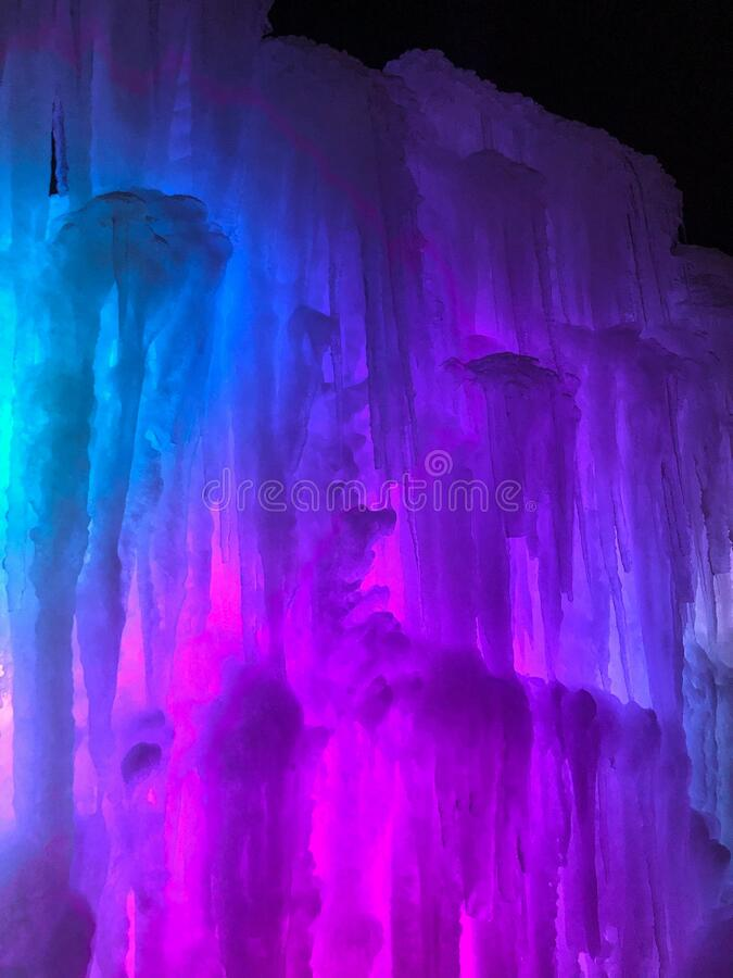 Multi-colored lighted icicle walls in ice castle. These colorful blue and purple lighted icicles are glowing in the night sky.  The ice castle in Lake Geneva stock image