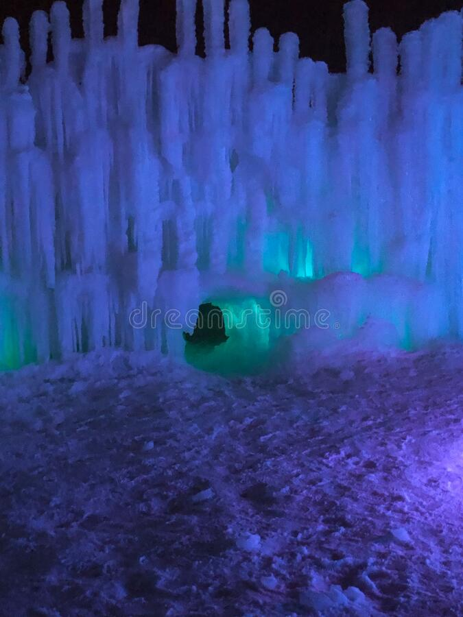 Multi-colored lighted icicle walls in ice castle. These colorful lighted icicles are glowing in the night sky.  The ice castle in Lake Geneva, Wisconsin is made stock image