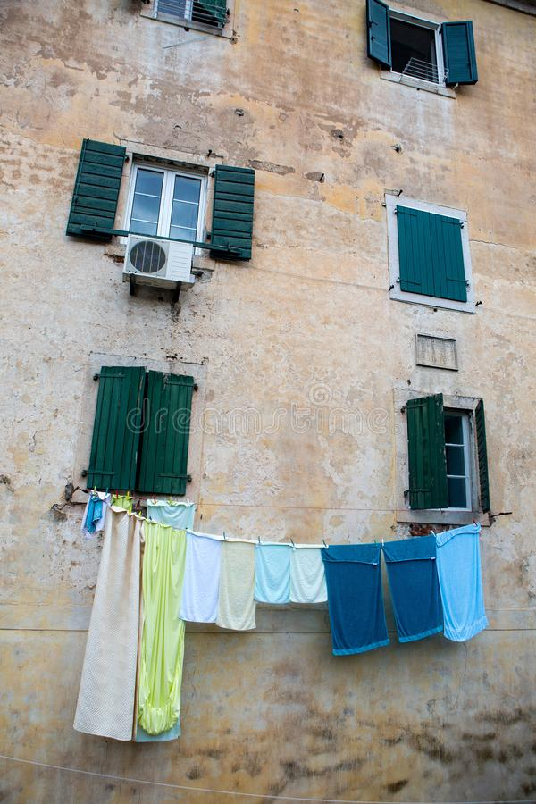 Multi-colored linen is dried outside the window of an old house royalty free stock photography
