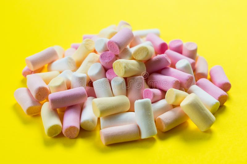 Multi-colored little marshmallows on a bright yellow background. royalty free stock photos