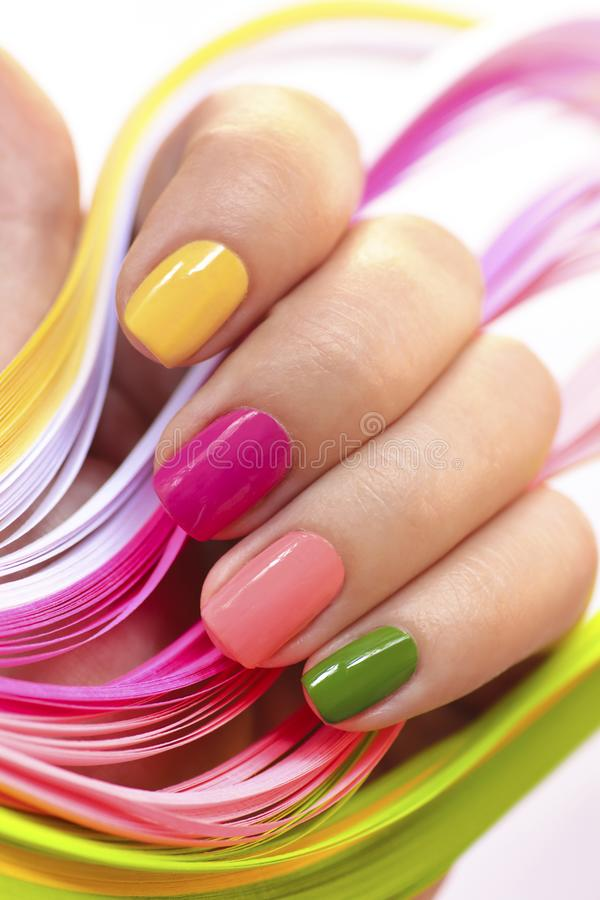 Multi-colored manicure with pink,green, yellow and peach nail Polish stock image