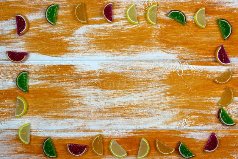 Multi-colored marmalade in the form of citrus slices laid out as a frame on an orange Board royalty free stock images