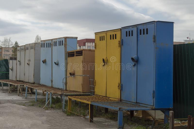 Multi-colored metal cabinets standing on the territory of the industrial zone royalty free stock images