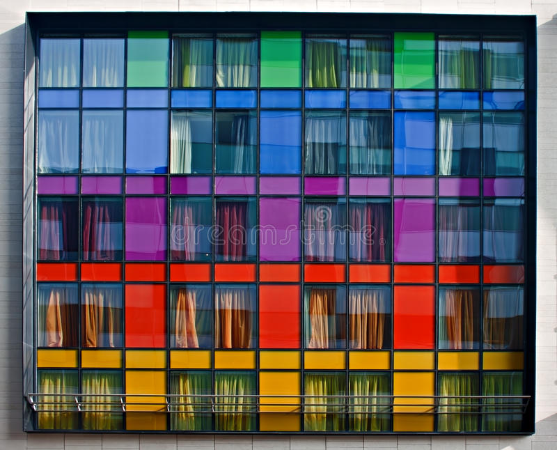 Multi-colored modern apartment building. Windows stock image