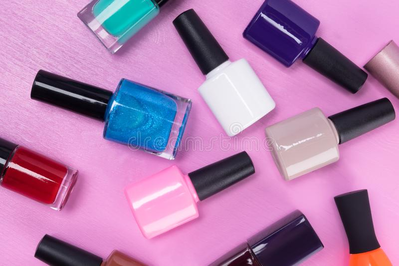 Multi-colored nail polishes on a pink background, close-up royalty free stock photos