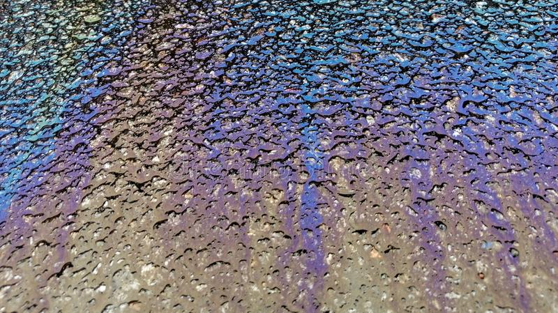 Multi colored oil spill on asphalt road, abstract background. Texture stock photo