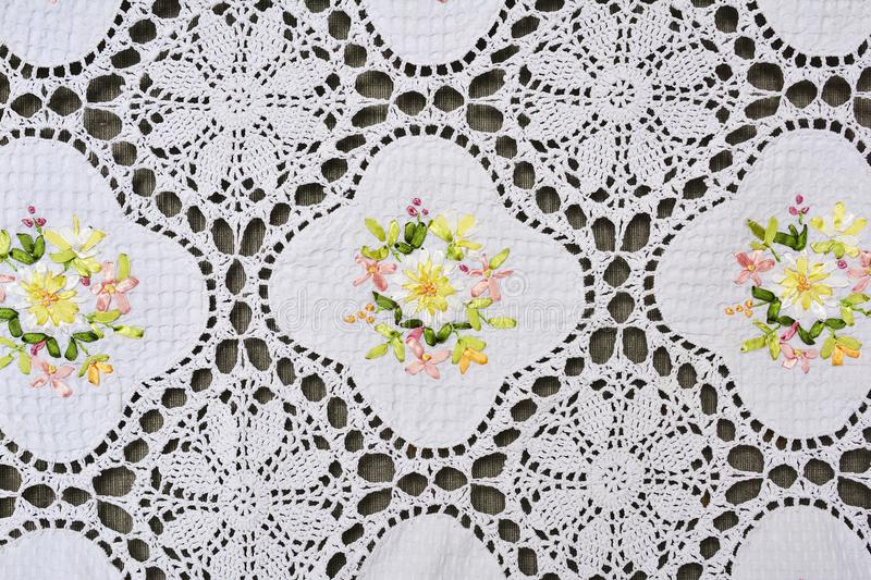 Multi-colored ornate floral pattern on white cotton lace tablecloth. Background stock images