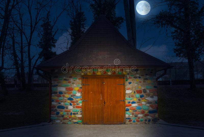 Multi-colored painted little house at night with full moon.  Colorful stone house like in fairy tales stock images
